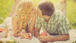 Married couple about to kiss during a picnic