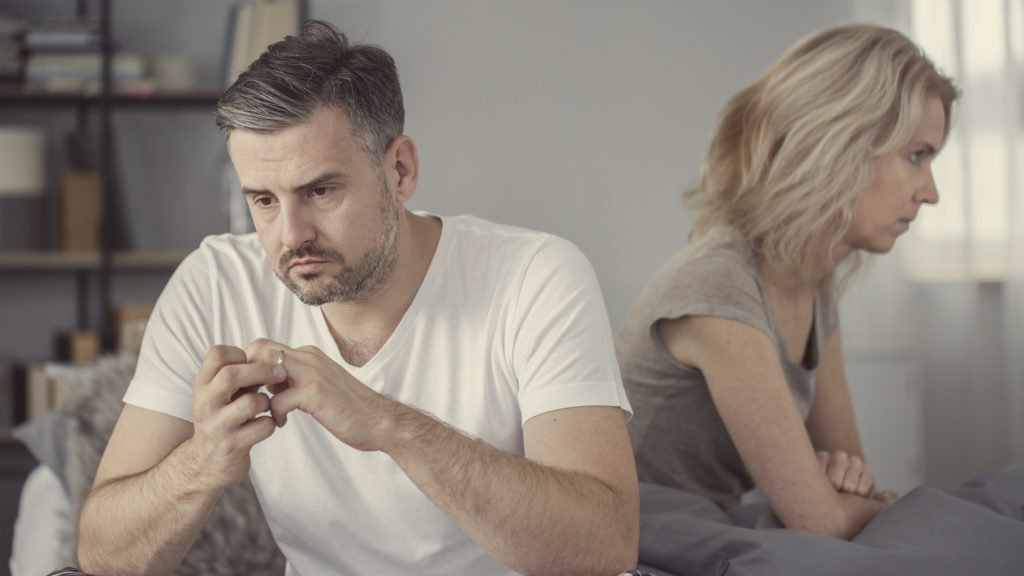 Depressed middle-age couple seated in different directions. He's toying with his wedding band, implying a troubled marriage