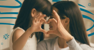 Mother and daughter making a heart with their hands