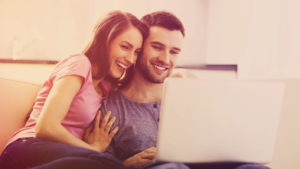 Couple sitting together smiling at a computer