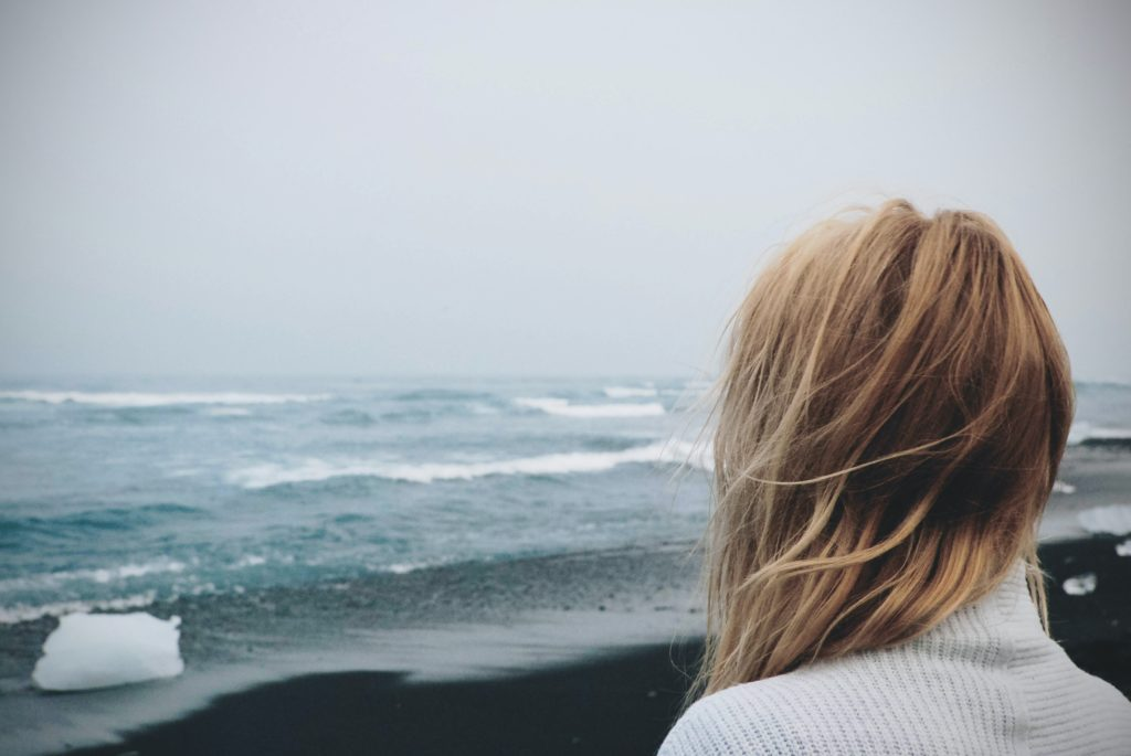 Shown from behind, a woman standing on a beach, looking out over the ocean on a cloudy day