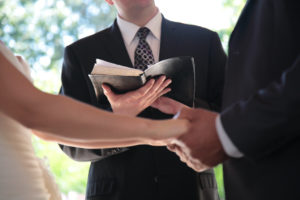 Photo of a pastor conducting a wedding with the married couple holding hands.
