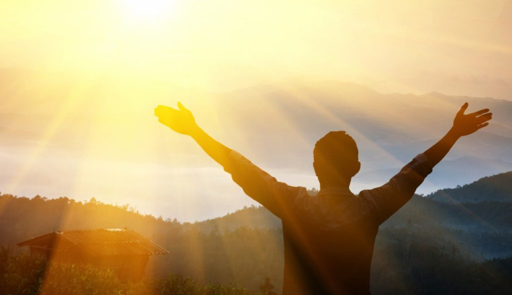 Shown from behind, a silhouette of a young man standing on a hill raising his arms toward the sunrise over the mountains