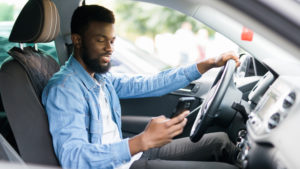 Young man looking at phone inside car
