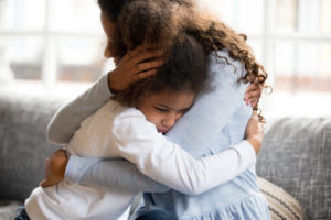 foster mom hugging child from hard place