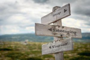Stop sabotaging yourself text engraved on an old wooden signpost.