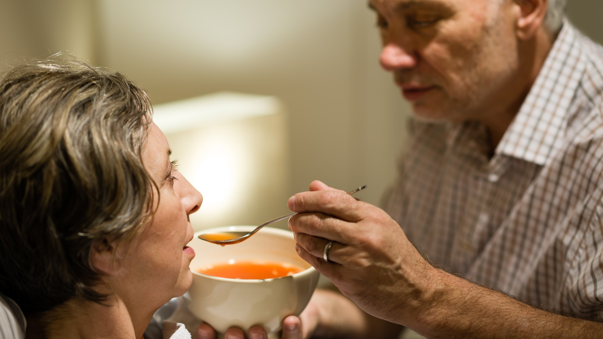 Husband feeding his wife some soup as she lies sick in bed