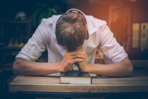 Photo of a pastor, head down, praying over a Bible.