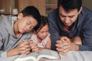 Father and his two young children praying together at a bedside with an open bible in front of them