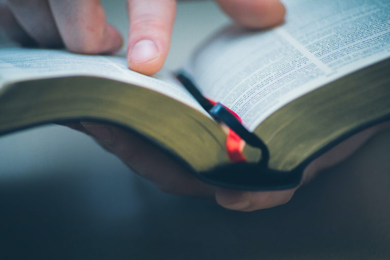 Photo of someone scanning the Bible with their finger.