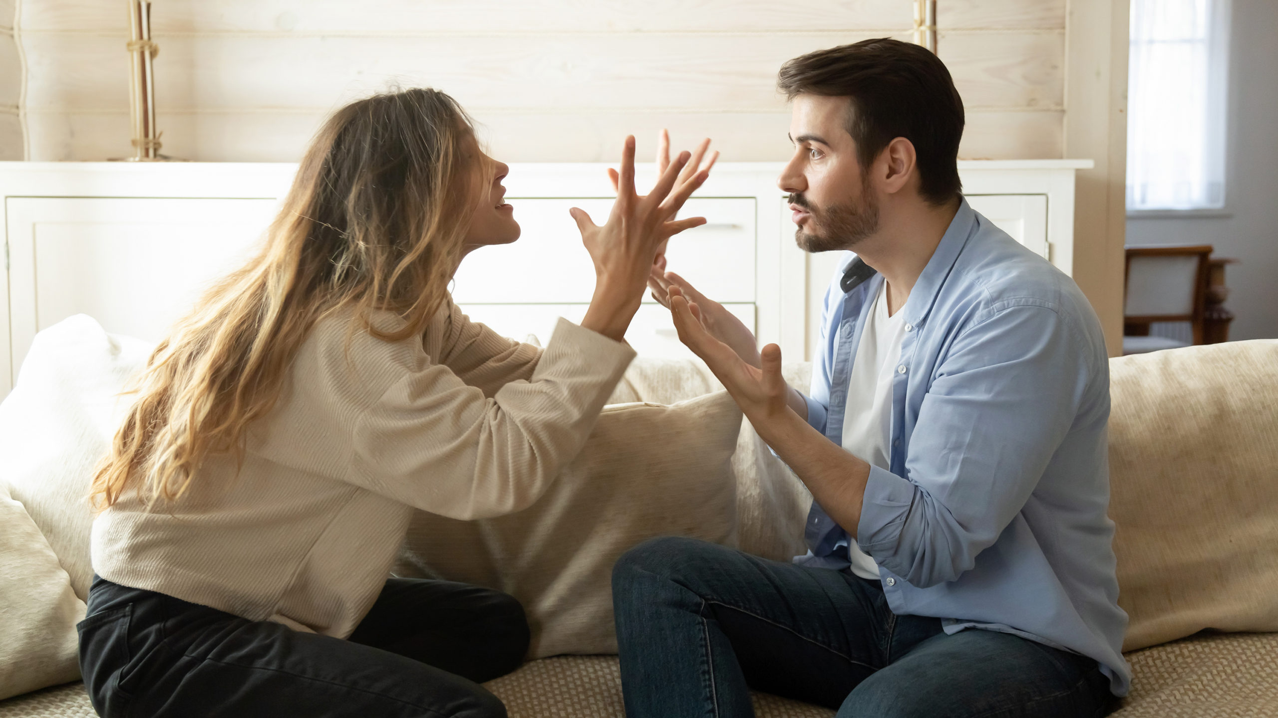 Young couple arguing on a couch about annoying habits