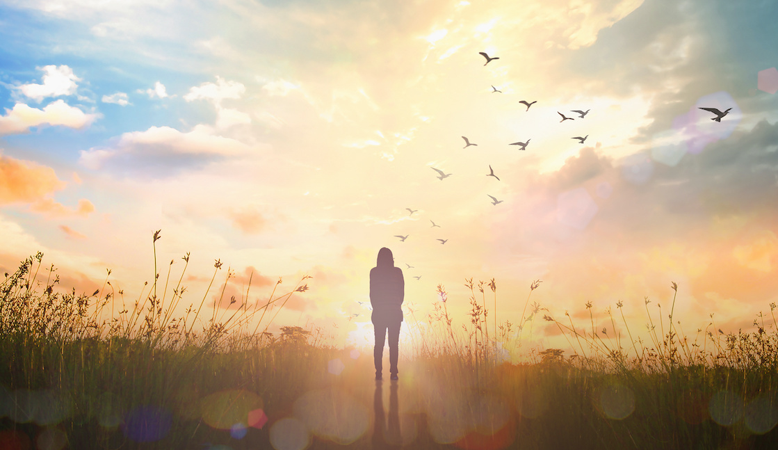 A woman looks at a bright sunset, pondering bible verses on death and suffering.