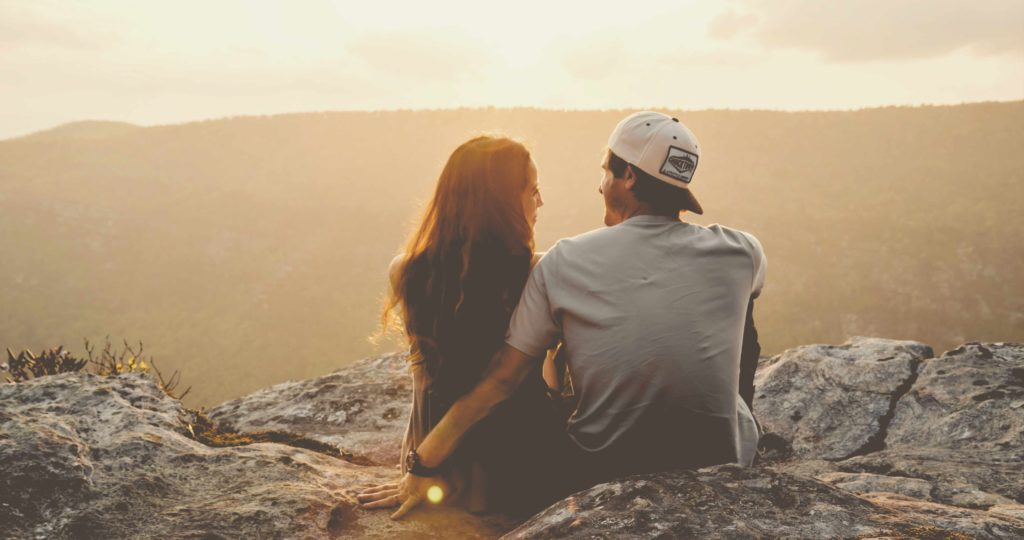 photo-man-and-woman-sitting-together-outside-looking-at-view-of-landscape