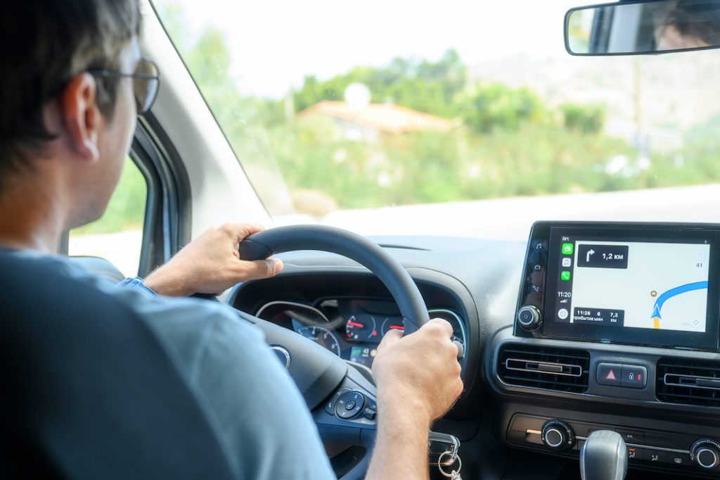 Photo of a man at a steering wheel, following a GPS map.
