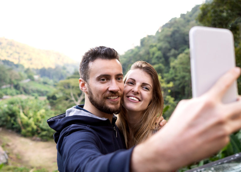 Photo-young-couple-take-selfie-at-sunset-in-mountains