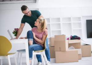 Photo-young-couple-moving-into-home-with-boxes-around-them