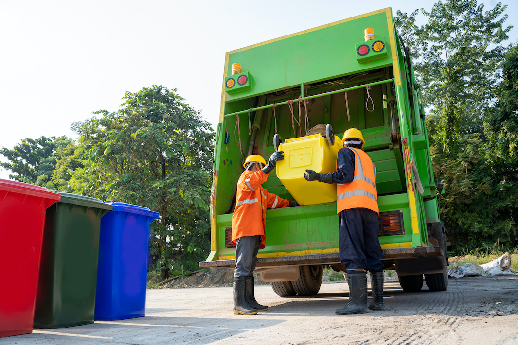 Two sanitary workers dump a trash can into a garbage truck.