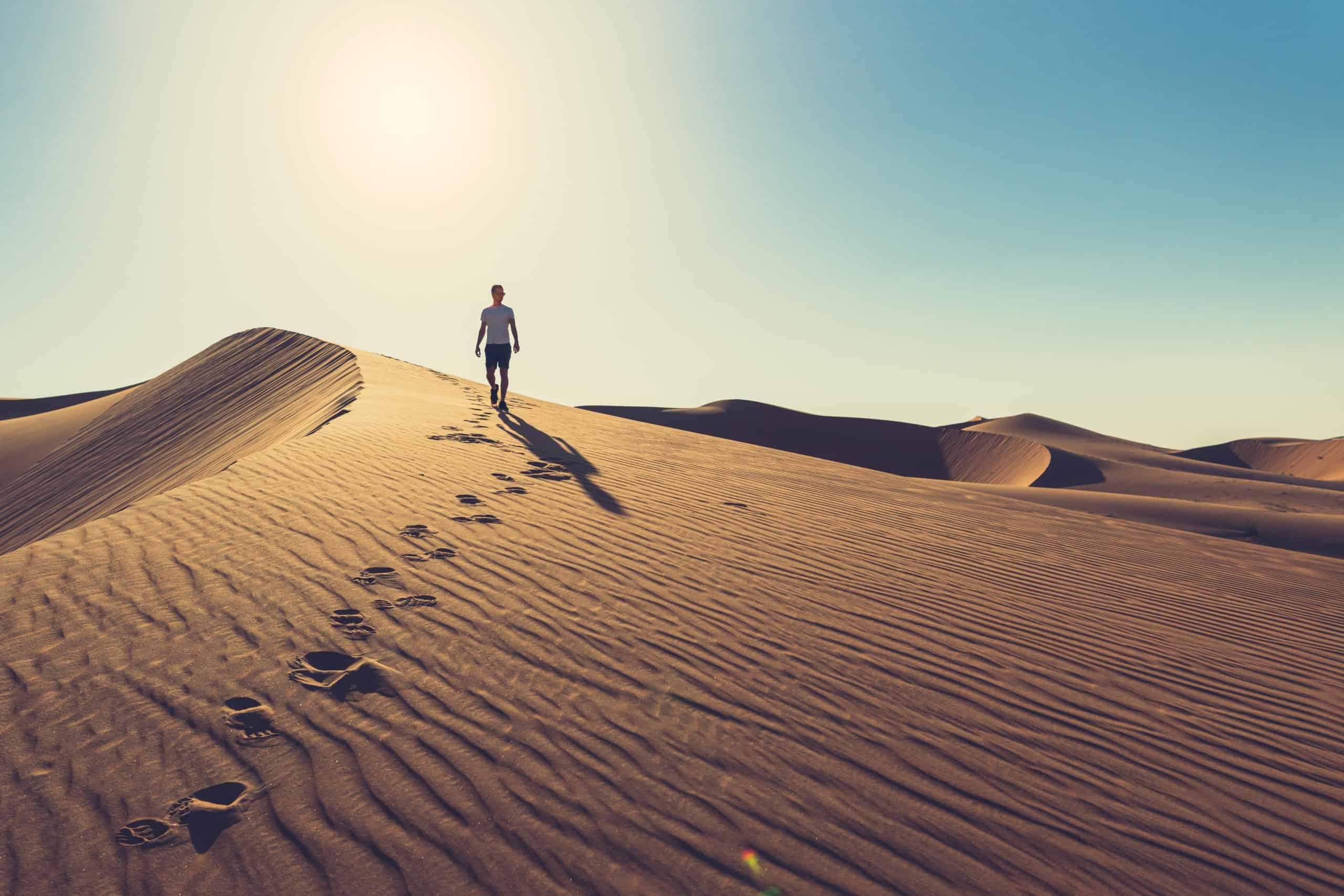 Photo of a man wandering through a desert.