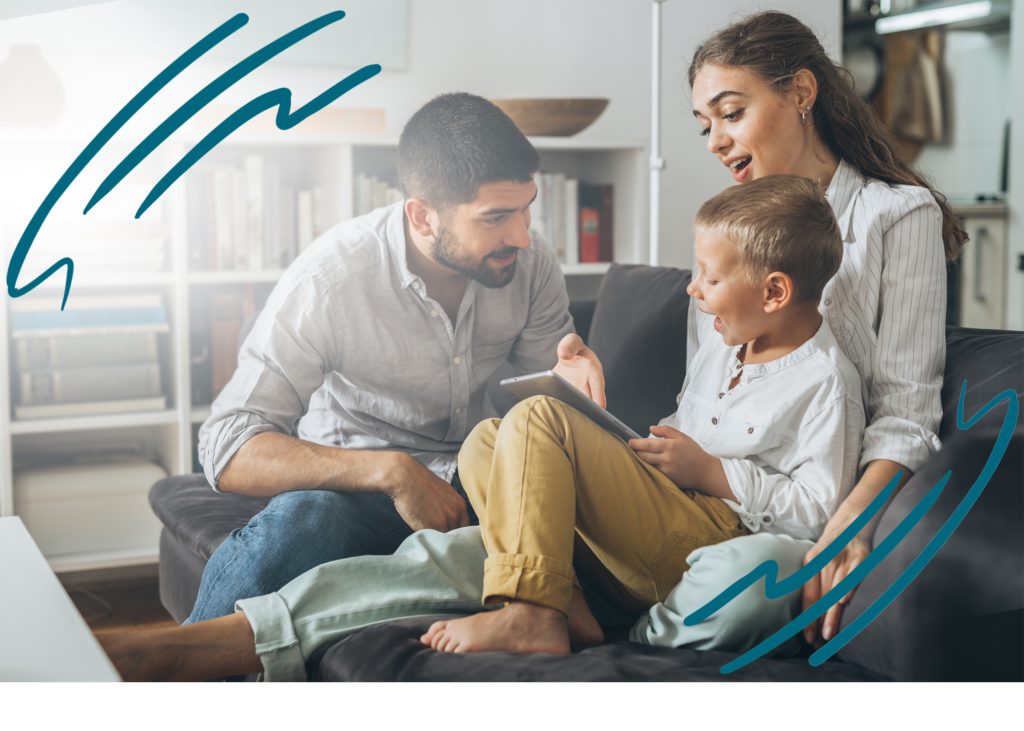 Young boy holding a tablet in his lap, sitting on a couch together with his mom and dad as they explain something to him
