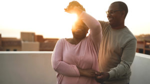 Middle aged African American couple dancing on a rooftop at sunset