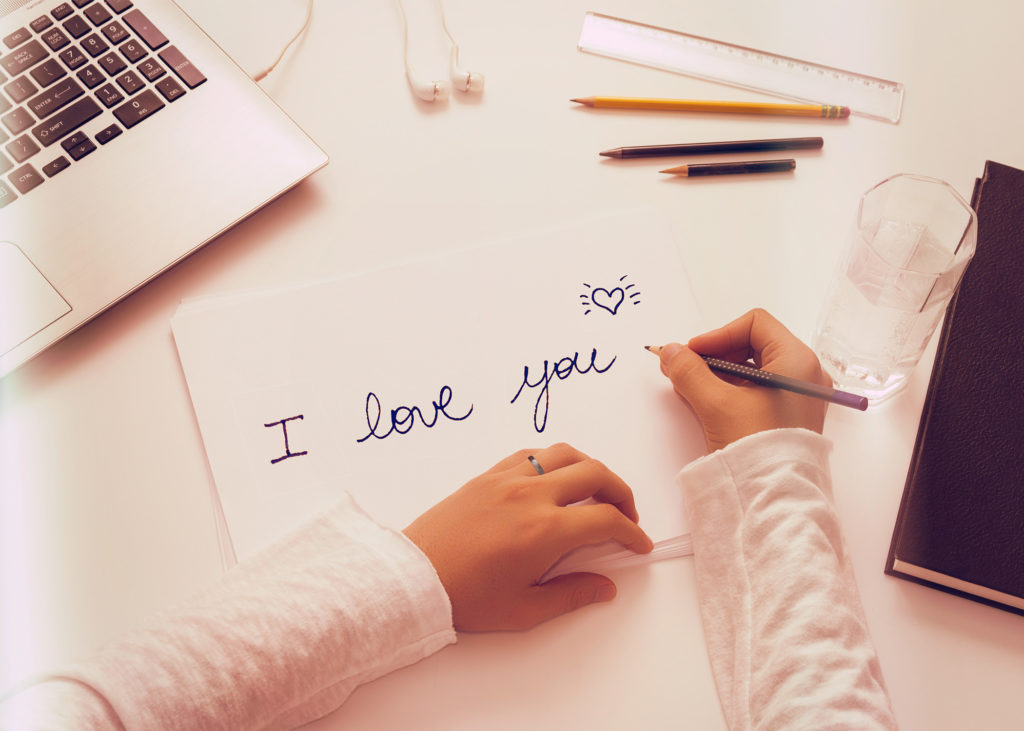 hands-writing-a-love-letter-on-paper