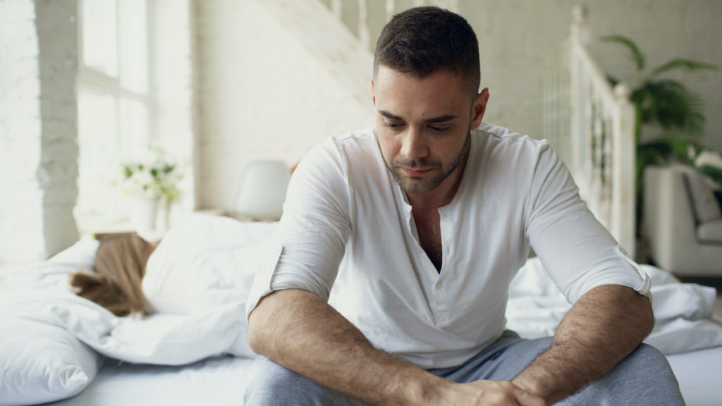 a man in white shirt sits on bed thinking with woman sleeping in background wondering should men have say in abortion