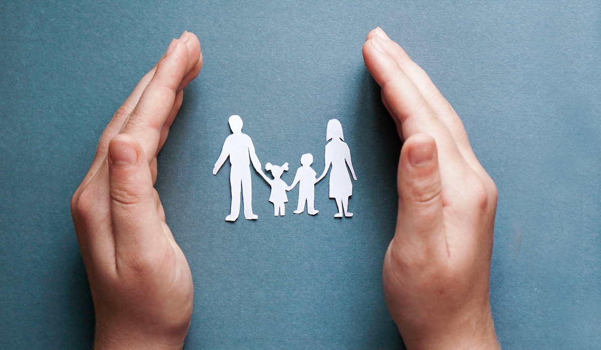 Hands of a boy ground a paper-cut family on blue background for discussing open adoption and family.