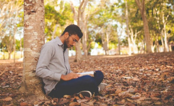 Young man sitting on the ground at the base of a tree studying the Bible