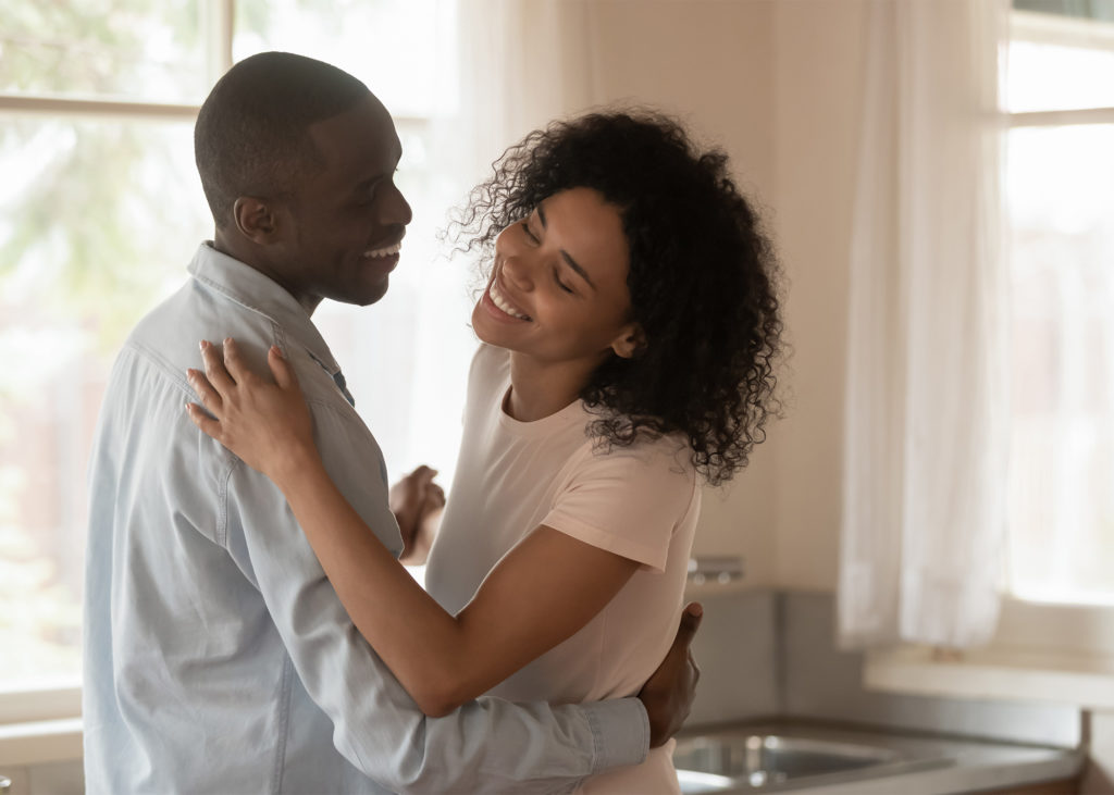 Happy-young-African-American-couple-dancing-in-living-room